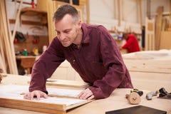 Carpinteiro Looking At Plans na oficina Imagem de Stock