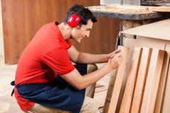 Carpinteiro Marking On Plank com lápis imagem de stock
