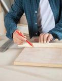 Carpinteiro Marking On Wood com lápis fotografia de stock royalty free