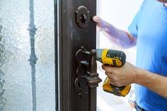 Carpinteiro masculino do trabalhador manual na instalação interior da fechadura da porta do metal fotografia de stock royalty free
