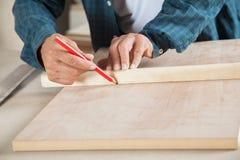 Carpinteiro masculino Marking On Wood com lápis foto de stock
