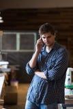 Carpinteiro masculino na loja da carpintaria no telefone, homem no trabalho, lif imagens de stock royalty free
