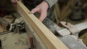 Carpinteiro masculino que trabalha com a máquina de aplanamento na oficina vídeos de arquivo