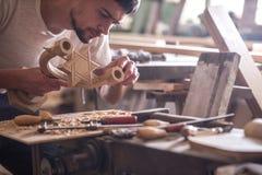 Carpinteiro masculino que trabalha com um produto de madeira, ferramentas da mão Fotografia de Stock