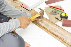 Carpinteiro masculino que usa o martelo e o prego no lugar de trabalho Ferramenta do artesão do fundo Imagens de Stock Royalty Free