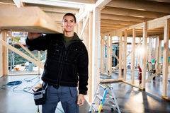 Carpinteiro masculino With Wooden Plank no canteiro de obras foto de stock