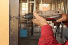 Carpinteiro na instalação da porta com broca elétrica Foto de Stock