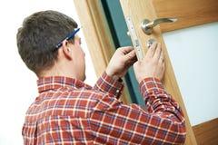 Carpinteiro na instalação da fechadura da porta Fotografia de Stock