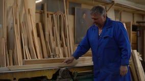 Carpinteiro no trabalho em sua oficina, processamento de madeira em uma máquina do woodworking video estoque