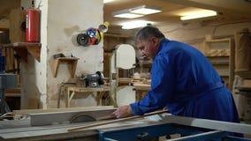 Carpinteiro no trabalho em sua oficina, processamento de madeira em uma máquina do woodworking vídeos de arquivo