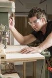 Carpinteiro no trabalho no trabalho usando a ferramenta elétrica Imagens de Stock