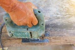 Carpinteiro ou marceneiro que trabalham com serra elétrica - close up nas mãos, carpinteiro na natureza, carpinteiro em Tailândia Imagens de Stock Royalty Free