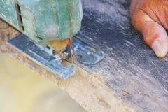 Carpinteiro ou marceneiro que trabalham com serra elétrica - close up nas mãos, carpinteiro na natureza, carpinteiro em Tailândia Fotos de Stock Royalty Free