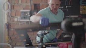 Carpinteiro profissional do retrato que corta uma parte de madeira em sua oficina da carpintaria, usando uma serra circular com o filme