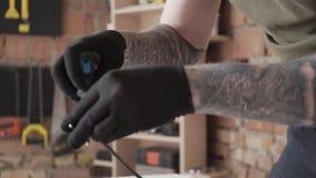 Carpinteiro profissional no tampão que trabalha com fios elétricos perto acima A muito utiliza ferramentas para a fabrica??o da m filme