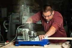 Carpinteiro profissional que trabalha com máquina de sawing Fotografia de Stock
