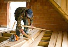 Carpinteiro que constrói o assoalho novo de uma sala do sótão imagens de stock
