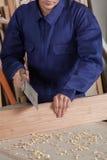 Carpinteiro que corta uma parte de madeira Imagens de Stock Royalty Free