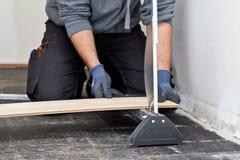 Carpinteiro que corta uma placa de assoalho para a instalação Fotos de Stock