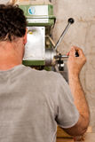 Carpinteiro que fura uma prancha com maquinaria Imagens de Stock
