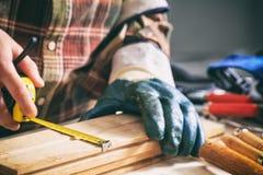 Carpinteiro que guarda uma medida da fita foto de stock