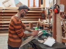 Carpinteiro que marca o detalhe na oficina foto de stock