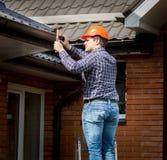 Carpinteiro que martela placas do telhado com martelo Imagens de Stock