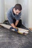 Carpinteiro que mede placas de assoalho de madeira novas Imagens de Stock Royalty Free