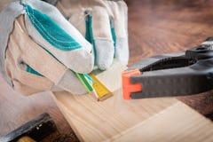 Carpinteiro que mede uma prancha de madeira Imagem de Stock