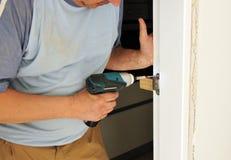 Carpinteiro que parafusa a trava de uma porta Fotografia de Stock Royalty Free