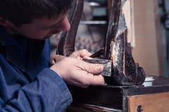 Carpinteiro que restaura a mobília de madeira com emplastro e massa de vidraceiro Knif imagem de stock
