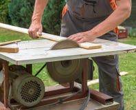 Carpinteiro que trabalha com a serra elétrica do zumbido imagem de stock