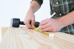 Carpinteiro que usa a medida da fita marcar na prancha Fotografia de Stock Royalty Free