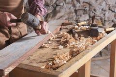 Carpinteiro que usa o formão para alisar abaixo da madeira fotos de stock royalty free