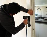 Carpinteiro que usa um nailer do ar comprimido para introduzir pregos no conjunto de uma porta deslizante Fotos de Stock Royalty Free