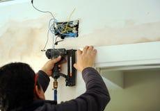 Carpinteiro que usa um nailer do ar comprimido para introduzir pregos no conjunto de uma porta deslizante Fotografia de Stock Royalty Free
