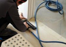 Carpinteiro que usa um nailer do ar comprimido para introduzir pregos no conjunto de uma porta deslizante Imagens de Stock Royalty Free