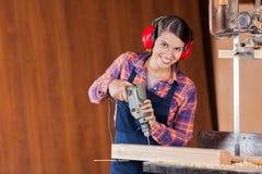 Carpinteiro seguro Using Drill Machine dentro imagens de stock