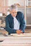 Carpinteiro superior Marking On Wood com lápis imagens de stock royalty free