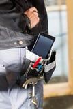 Carpinteiro With Tablet Computer e ferramentas no saco no local Fotografia de Stock Royalty Free