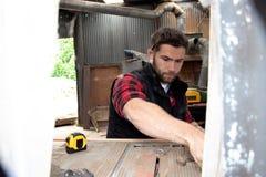 Carpinteiro, trabalho de madeira do trabalhador que mede, furando e fazendo o produto da madeira imagem de stock royalty free