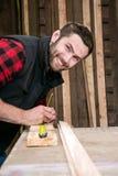 Carpinteiro, trabalho de madeira do trabalhador que mede, furando e fazendo o produto da madeira foto de stock royalty free