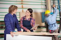 Carpinteiros com tabuleta de Digitas que discutem dentro imagem de stock royalty free