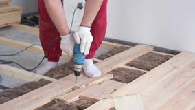 Carpintería en la casa - un varón profesional joven monta un piso de madera de pino metrajes