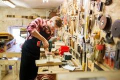 Carpintero con el tablón de la perforación del taladro en el taller Imágenes de archivo libres de regalías