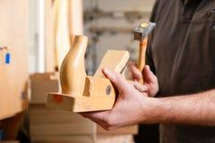 Carpintero con la alisadora y el martillo de madera Foto de archivo libre de regalías