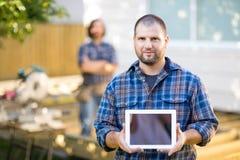 Carpintero confiado Displaying Digital Tablet con imágenes de archivo libres de regalías