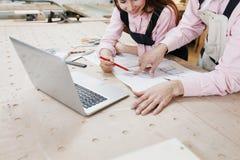 Carpintero de la empresaria que trabaja en el ordenador port?til en superficie de madera entre las herramientas de la construcci? imagen de archivo