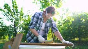 Carpintero de la mujer que pela apagado el tablón de madera viejo con el cepillo del metal en patio trasero almacen de metraje de vídeo