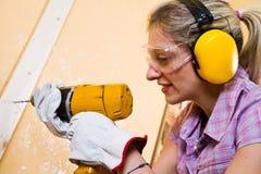 Carpintero de sexo femenino en el trabajo usando la máquina del sondeo a mano foto de archivo